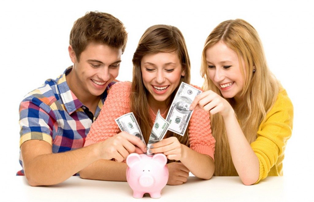Teens putting money into a piggy bank